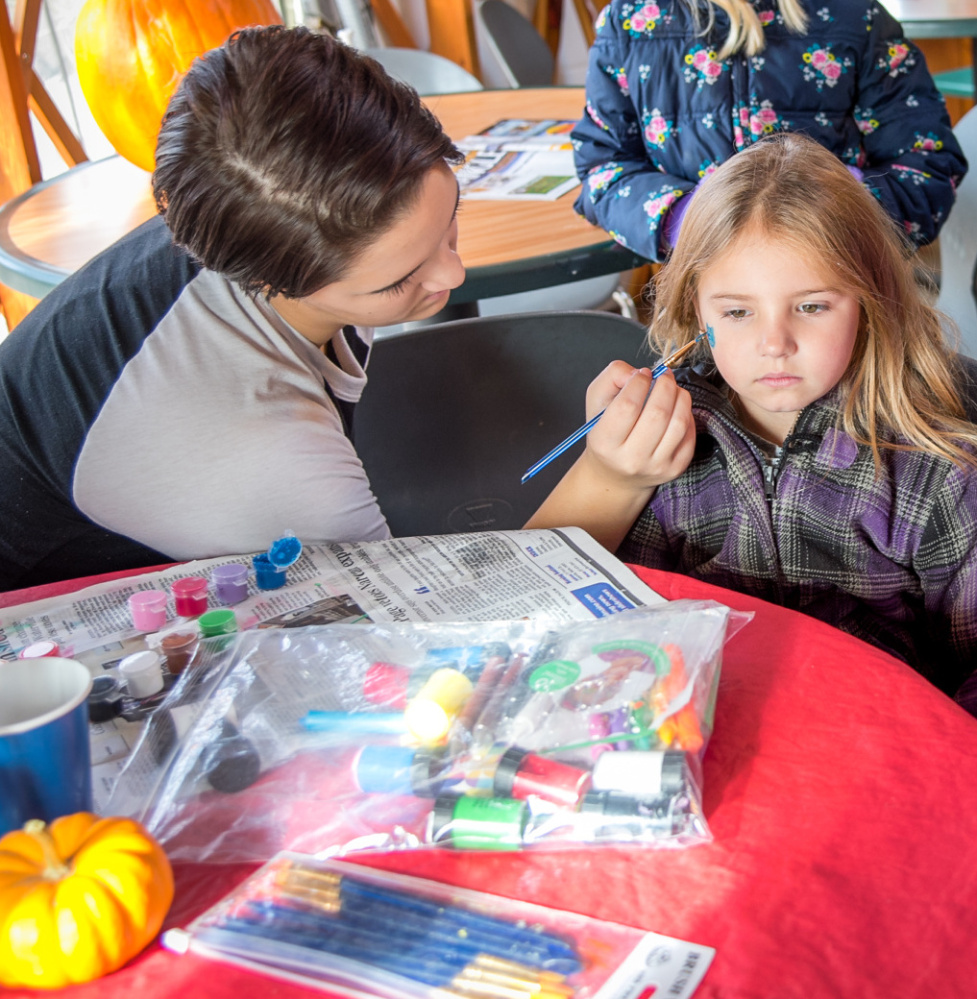 Brenna Rolfe gets a cat painted on her face Saturday by Fall Festival volunteer Cailynn Colby at the Quarry Road Trails recreation area.
