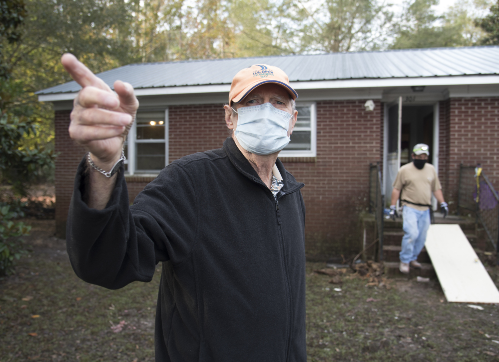 Bill Jones, 77, stands outside his home that was heavily damaged by floodwater. Nearly a month since a flood  consumed the town, few have returned.