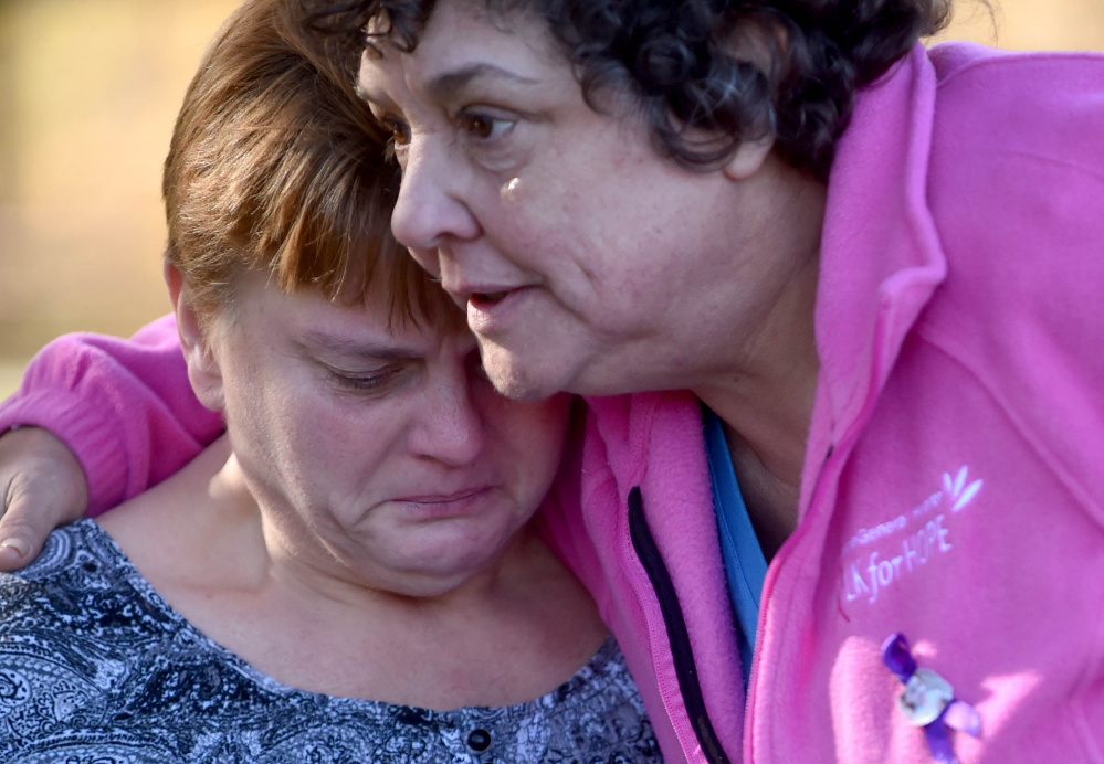 Jackie Bragg, left, is comforted by friend Carla Chaput as she reflects Friday on the lives of her daughters Amanda Bragg and Amy DeRosby at Mill Island Park in Fairfield.