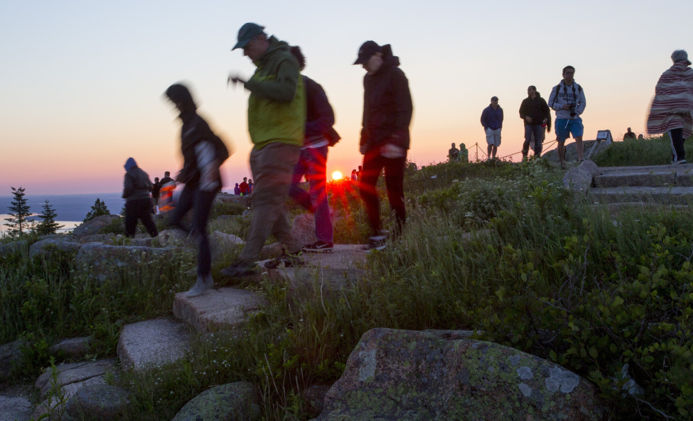 Visitors leave Cadillac Mountain after a glimpse of a sunrise in June. Officials at Acadia National Park are in the early stages of developing a strategy to confront traffic jams, crowds and parking shortages at the popular tourist attraction.