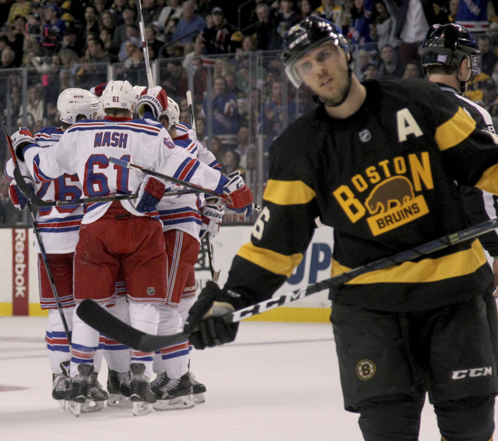 Rangers players surround Nick Holden after his first-period goal Saturday as Bruins center David Krejci reacts. New York won, 5-2.