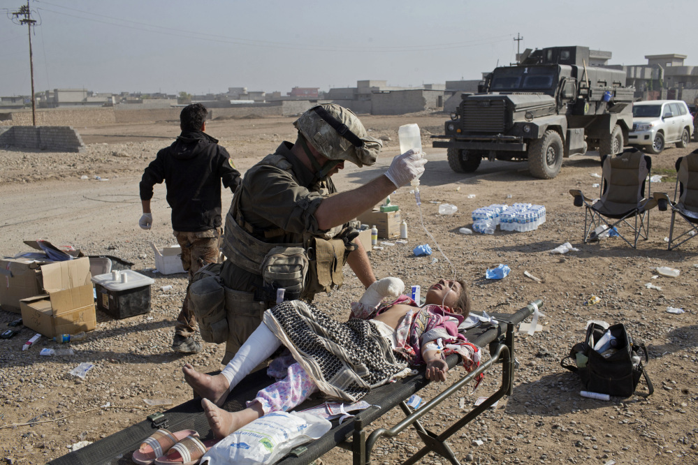 Derek Coleman, a volunteer medic, treats a wounded Iraqi special forces soldier at a field clinic in Gogjali, on the eastern outskirts of Mosul, Iraq, on Sunday.
