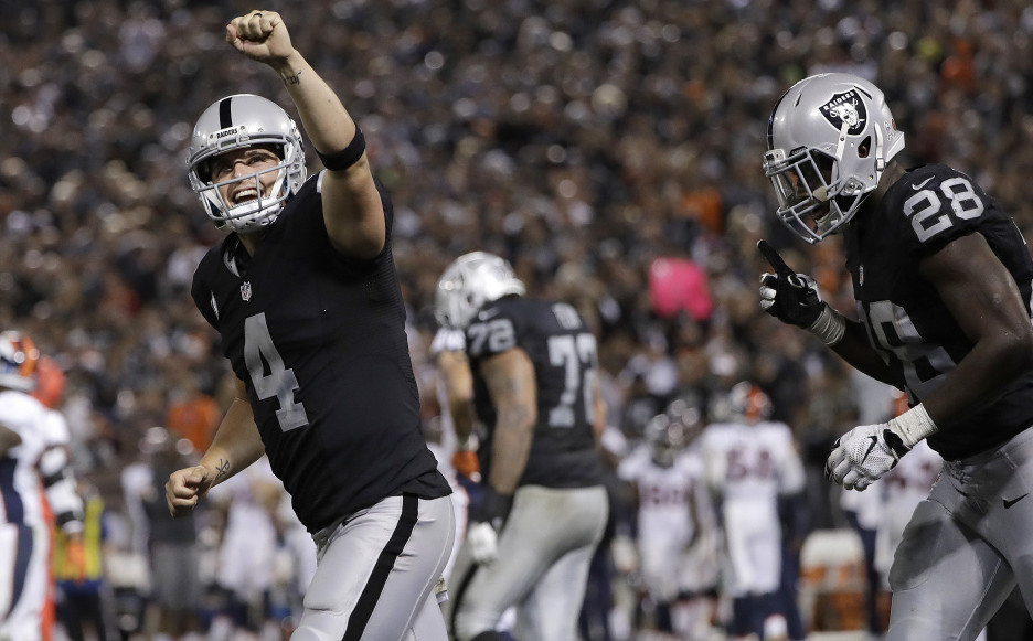 Oakland quarterback Derek Carr, left, celebrates a touchdown run by Latavius Murray, right, during the Raiders' 30-20 win over the Broncos on Sunday.