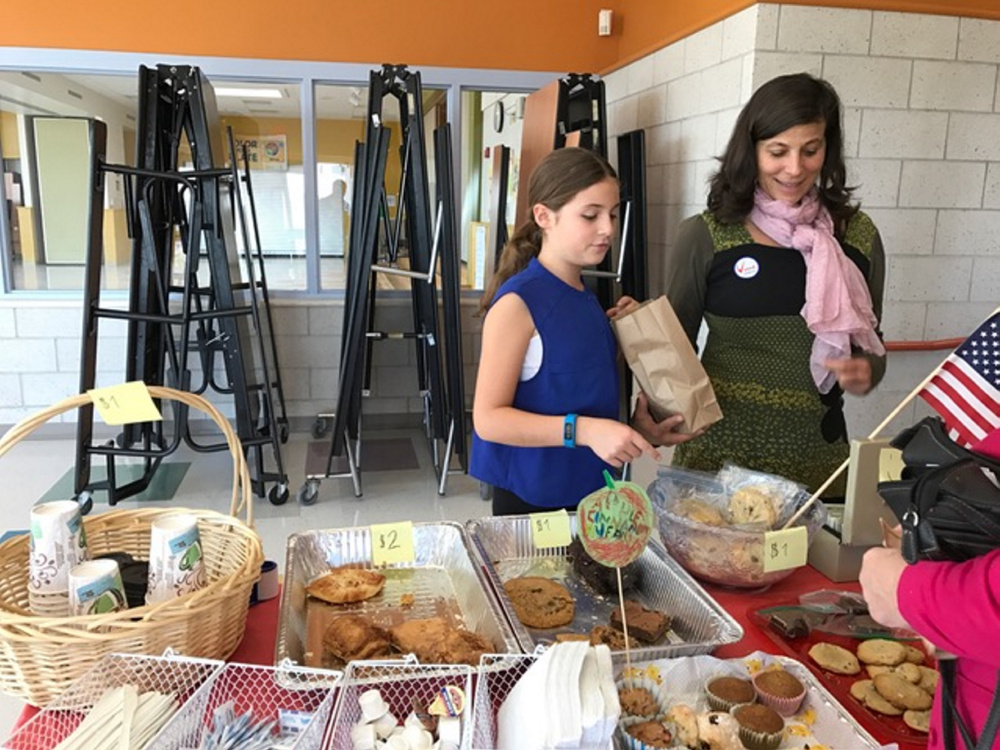 Naila Wissa and her daughter, fifth-grader Nora Grace Monaghan, man the treat table at East End Elementary School on Munjoy Hill.    Peggy Grodinsky/Food Editor