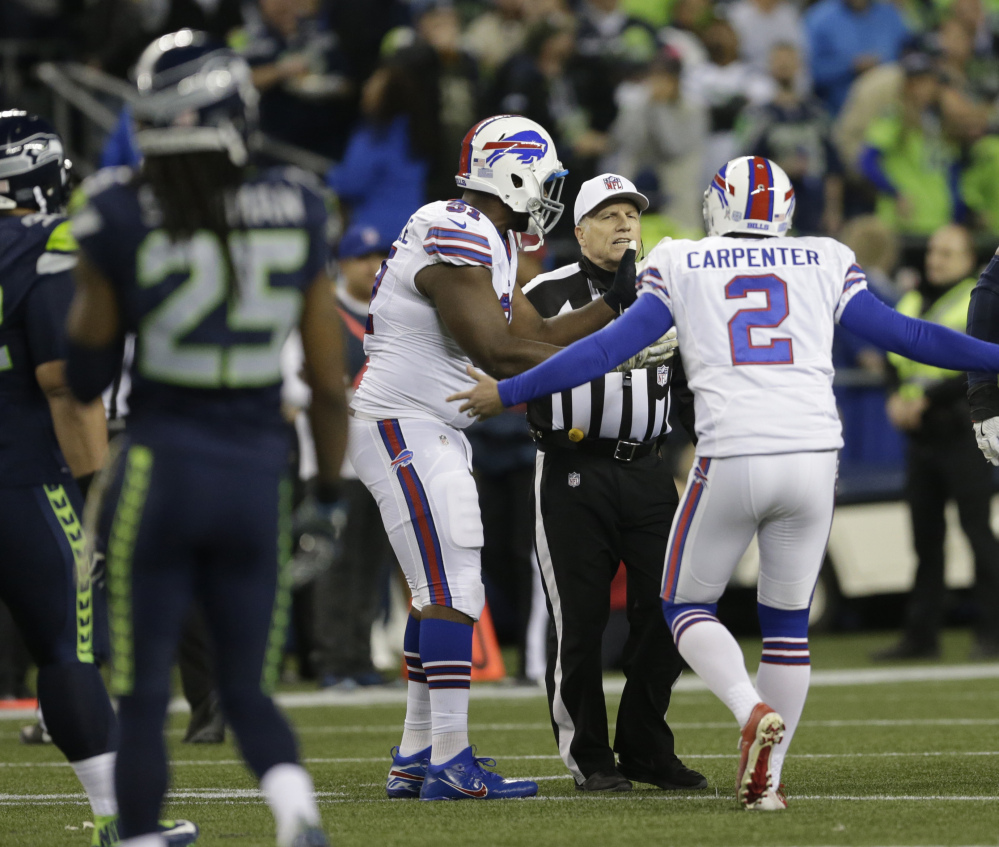 Kicker Dan Carpenter of the Buffalo Bills complains to referee Walt Anderson after being run into recklessly by Richard Sherman of Seattle. Only an offside call was made.