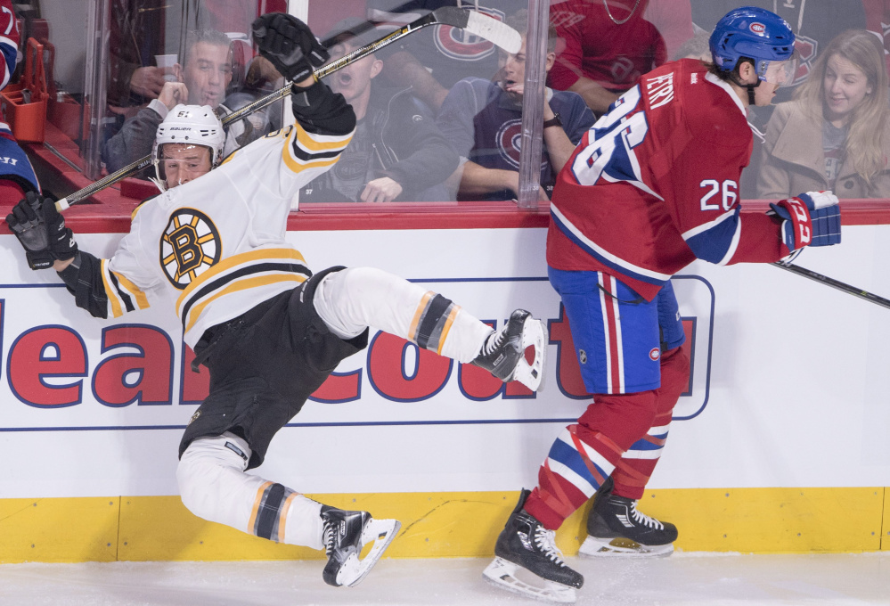 Boston's Ryan Spooner is checked into the boards by Montreal's Jeff Petry in the first period Tuesday night in Montreal. The Canadiens scored a late goal for a 3-2 win.