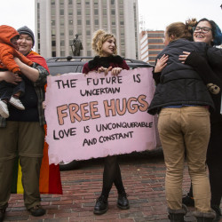 "Sophie McLeod, 22, holds Gabriel Hassan, 10 months, while his mom gets a hug from Stephanie Farinhas, 21, in Portland. Donald Trump's win left McLeod, Farinhas and Jackie King, center, 21, feeling down, so they decided to offer free hugs to passersby. ""I kind of needed one, so I figured everyone else could use one too,"" King said."