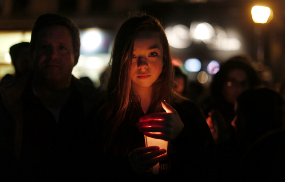 Portland resident Hannah Elizabeth Little holds a candle amid a crowd of hundreds of participants in Monument Square in Portland during a vigil to pledge unity Wednesday.