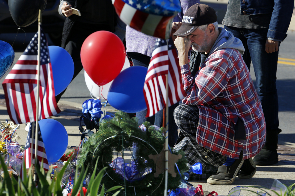 John Kelemen of Canonsburg, Pa., prays at a makeshift memorial after two Canonsburg, Pa., police officers were shot, one fatally, early Thursday in Canonsburg, Pa., by a man with a history of domestic abuse.