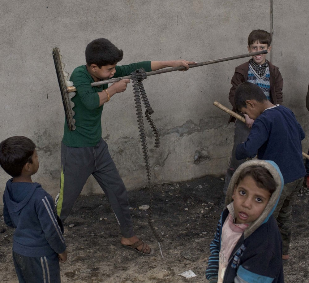 Children play in Qayara, some 50 kilometers south of Mosul, Iraq, on Thursday. Iraqi troops consolidated gains in their advance on the northern city of Mosul on Thursday, regrouping as they clear neighborhoods and houses once occupied by the Islamic State group. Associated Press/Marko Drobnjakovic