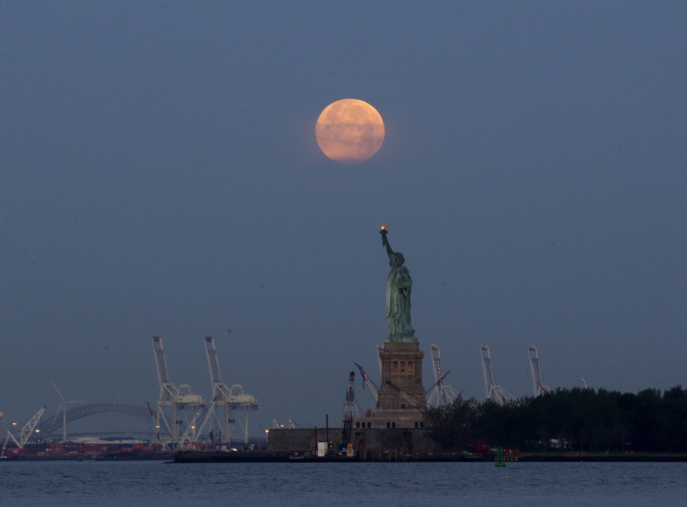 A supermoon rises over the Statue of Liberty in New York in 2013. Monday will have the closest full moon of the year, the closest the moon comes to us in almost 69 years.