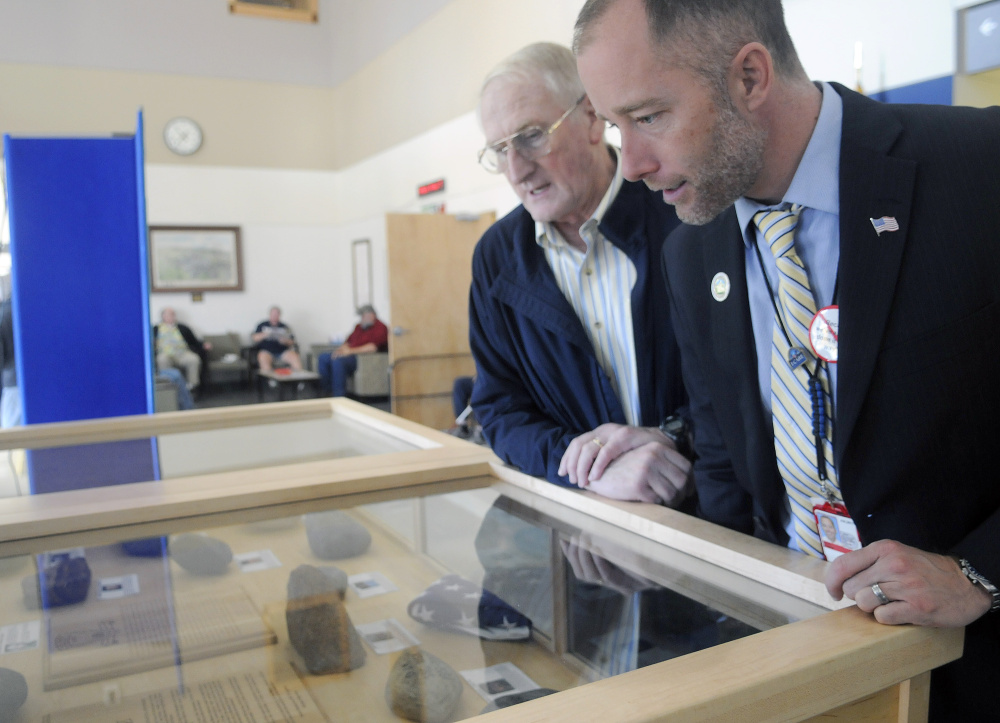 Veteran Peter Ogden, left, and Togus VA Director Ryan Lilly and examine stones on display Thursday at the Togus veterans hospital as part of the Summit Project. The engraved rocks commemorate military veterans who have died since Sept. 11, 2001.