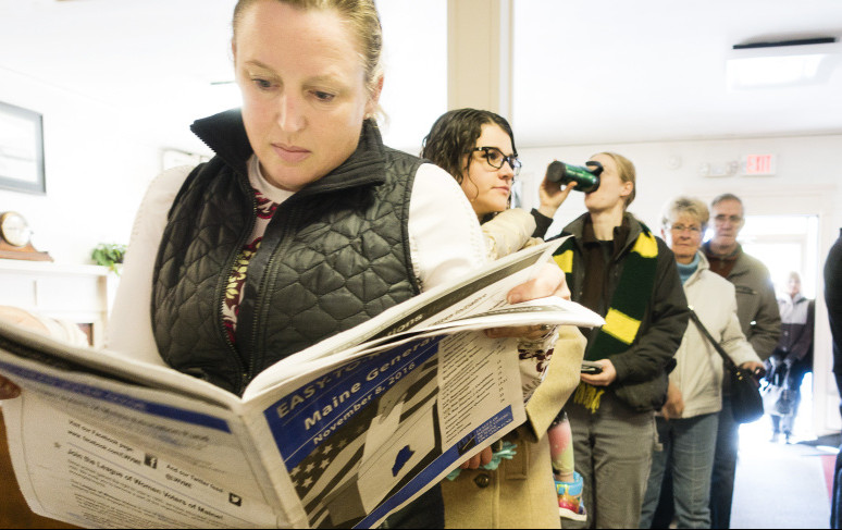 Karen Richards of Portland reads about ballot questions while waiting to vote Tuesday. The statewide vote leaves legislators with much work to do.