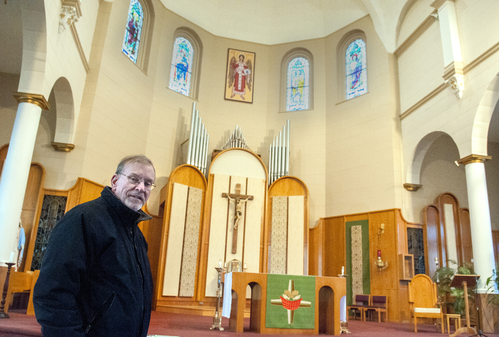 The Rev. Frank Morin stands in front of the altar Friday at St. Augustine Church in Augusta. The parish is celebrating the centennial of the opening of the church building.