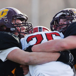Cape Elizabeth defenders Jacob Jordan, left, and Ryan Weare wrap up Wells running back Riley Dempsey in the first half of the Class C South championship game Saturday at Cape Elizabeth.