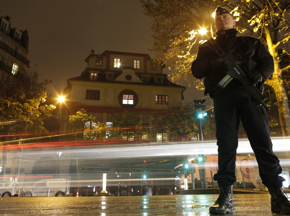 A policeman stands guard at the Bataclan concert hall in Paris on Saturday, where rock star Sting gave a special reopening concert and vowed,