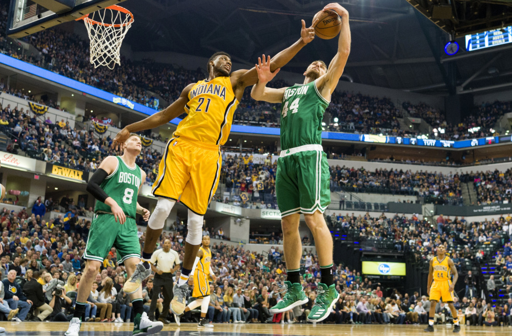 Tyler Zeller, right, of the Celtics attempts to keep a rebound away from Thaddeus Young of the Indiana Pacers during the first half of the Celtics' 105-99 victory Saturday night in Indianapolis.