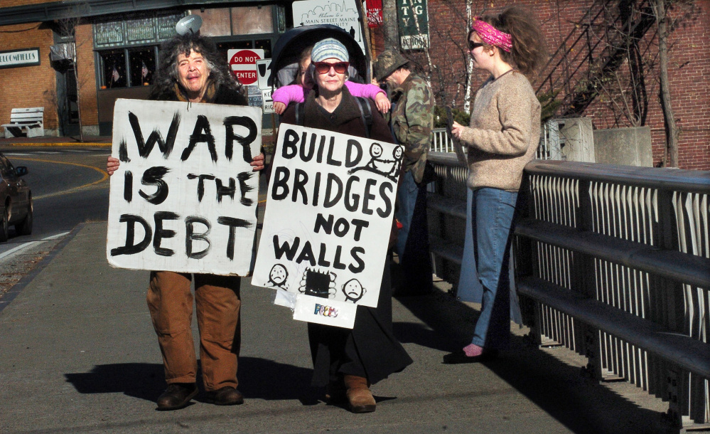 War protesters, from left, Abby Shahn, Lisa Savage and Selene Spivak and others hold signs Sunday on the Margaret Chase Smith bridge in Skowhegan. David Leaming/Morning Sentinel
