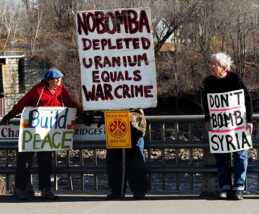 Lynne Harwood and Mark Roman make their case on a bridge in Skowhegan on Sunday. Some protesters have come there for a decade to advocate for a peaceful world. David Leaming/Morning Sentinel