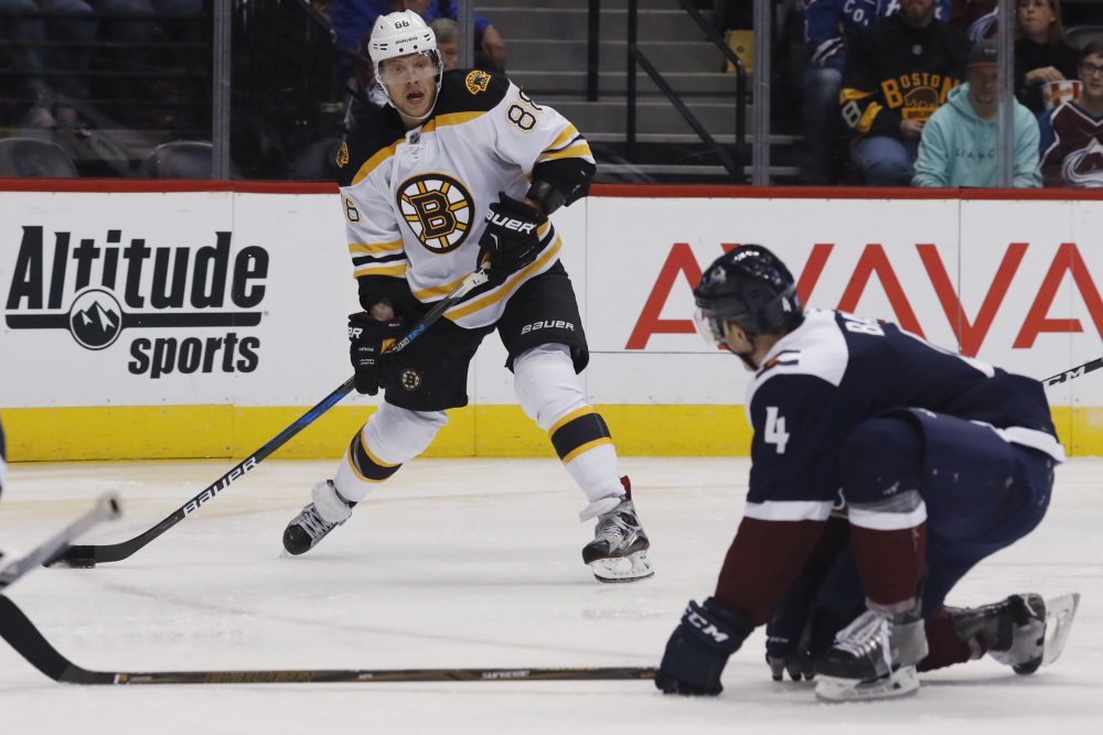 Bruins right wing David Pastrnak launches send a pass by Avalanche defenseman Tyson Barrie in the second period of Boston's 2-0 win Sunday in in Denver.