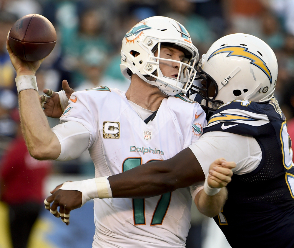 Dolphins quarterback Ryan Tannehill is hit by Chargers defensive end Corey Liuget as he tries to throw a pass Sunday in San Diego. Miami rallied for a 31-24 victory.