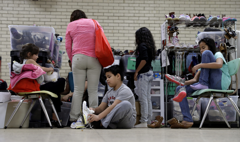 Central American migrants newly released after processing by the U.S. Customs and Border Patrol are fitted for shoes at the Sacred Heart Community Center in the Rio Grande Valley border city of McAllen, Texas, on Sunday.