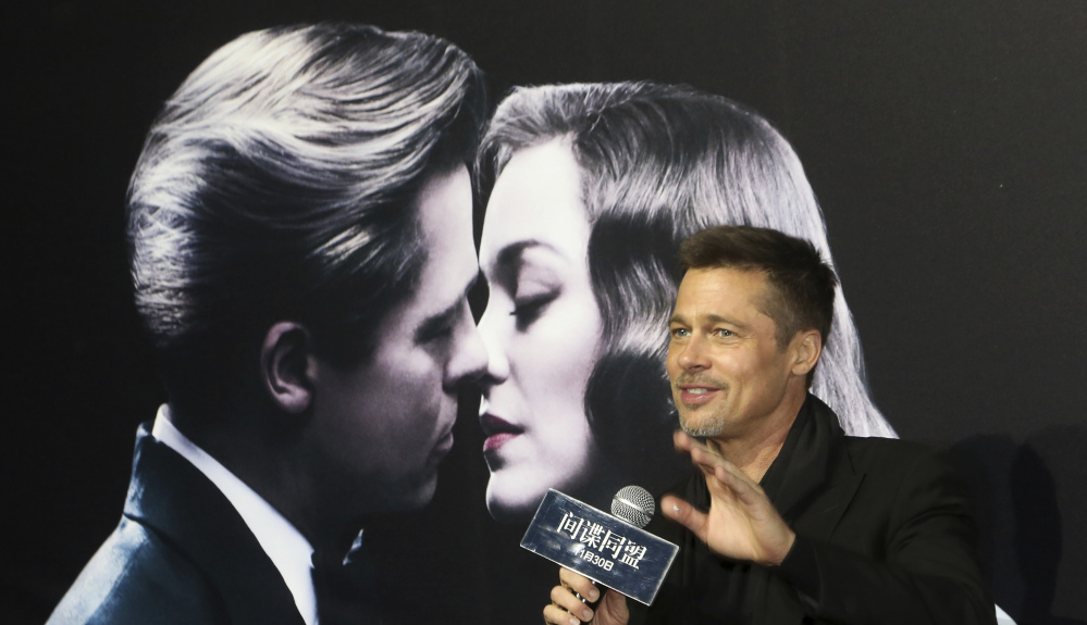 Actor Brad Pitt gestures to his fans as he attends a premiere of his film