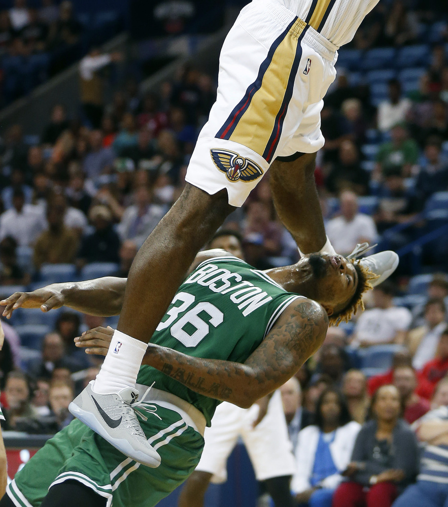 Pelicans forward Solomon Hill slam dunks over Celtics guard Marcus Smart in the first half Monday night. Hill was called for an offensive foul on the play.