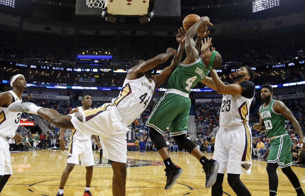 Celtics guard Isaiah Thomas battles under the basket with Pelicans forwards Anthony Davis (23) and Solomon Hill (44) in the first half of Monday night's game in New Orleans