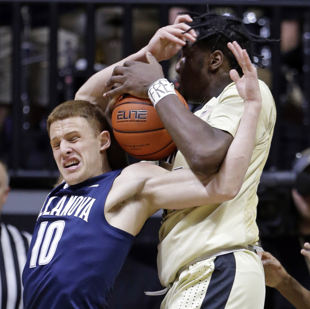 Purdue forward Caleb Swanigan, right, and Villanova guard Donte DiVincenzo battle for the ball in the first half of a 79-76 win by the Wildcats at West Lafayette, Ind., on Monday.