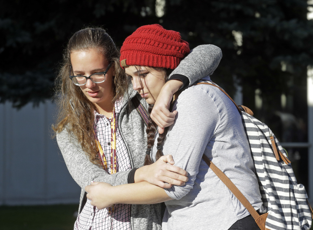 Students Albany Cox, right, and Holly Hilton leave Mountain View High School where several students were stabbed Tuesday in Orem, Utah. Police say a 16-year-old boy was taken into custody after the stabbings.
