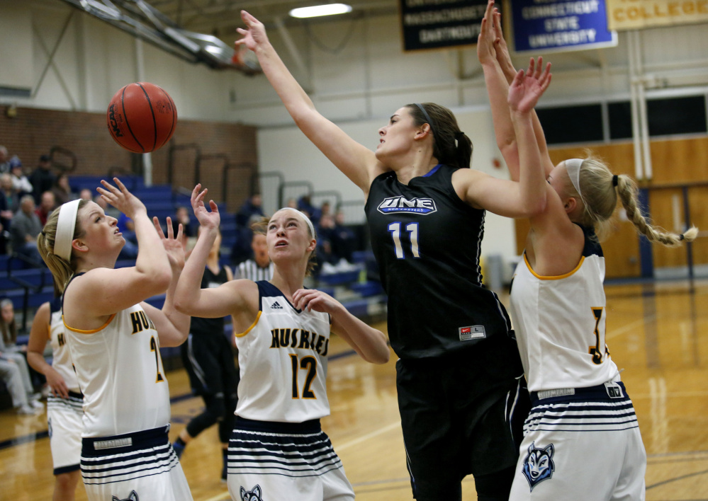 Alicia Brown of the University of New England, 11, battles for control of the ball with Kimberly Howrigan, left, Emily Nicholson and Chantel Eells, right, of USM during the first half of UNE's 62-46 victory in a women's basketball opener Tuesday night.