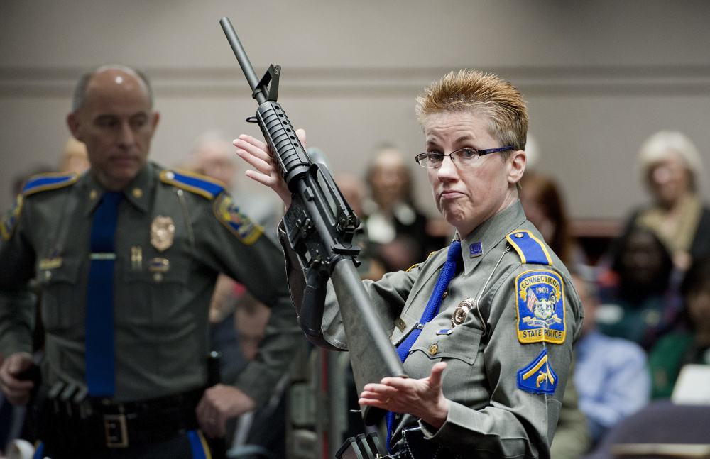 Firearms training unit Detective Barbara J. Mattson, of the Connecticut State Police, holds a Bushmaster AR-15 rifle, the same type of gun used in the Sandy Hook School shooting