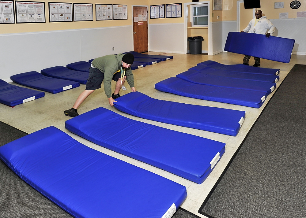 Brian Marchant, left, and Bonane Rutijanwa, attendants at the municipal homeless shelter in Portland, set up mats in a city office in 2013 for use if shelter space was filled. Historically, only about a third of clients at the shelter are Portland residents.