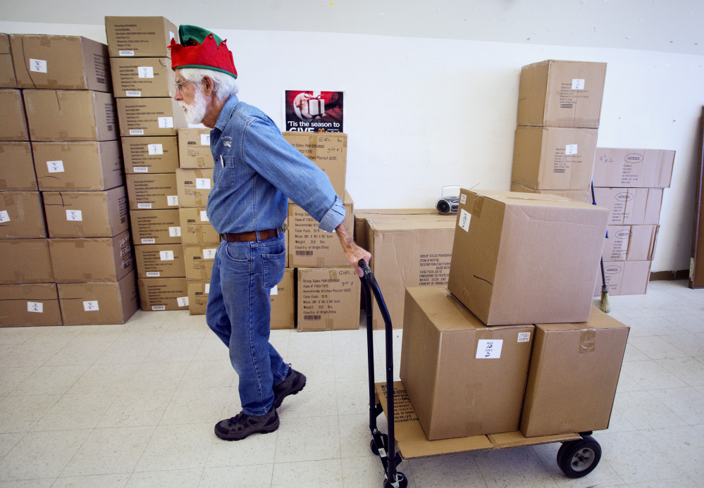 Carl Akin of Yarmouth, who is volunteering for his sixth year, moves boxes of packaged toys at the Toy Fund's processing center in Falmouth on Thursday.