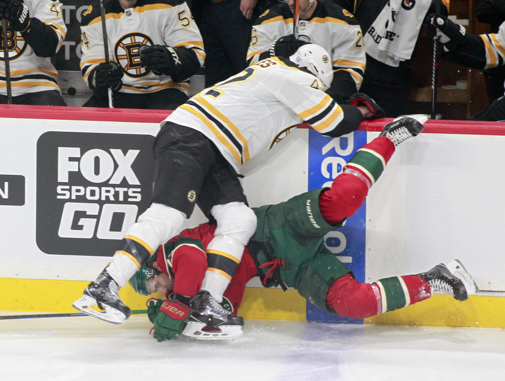 Minnesota's Nino Niederreiter is checked hard into the boards by Boston's David Backes in the first period Thursday night in St. Paul, Minn.