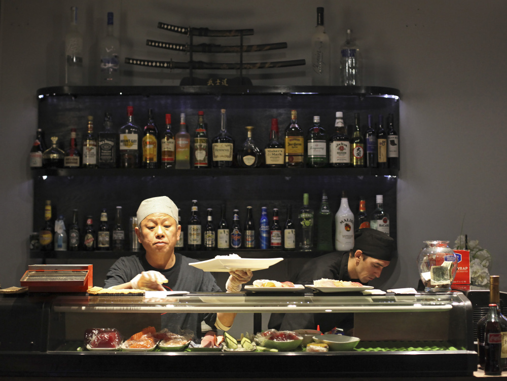 Duc Bui, owner and head sushi chef at Ginza Town, and Rick Roy, sushi chef, at work during the dinner hour.
