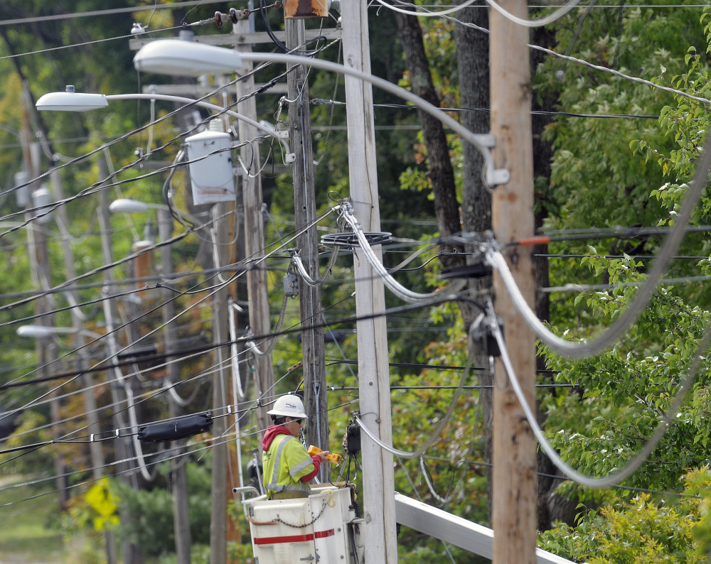 FairPoint lineman Scott Michaud works on a telephone line last year. FairPoint workers were notified Friday that more layoffs are coming. The telecommunications company endured a bitter four-month strike that ended in February 2015. Months later, the company laid off about 80 people in Maine and now another 35-49 are expected to be let go. The Charlotte-based company has had enduring troubles since purchasing Verizon's landline network in Maine, New Hampshire and Vermont  for $2.3 billion in 2007. (Andy Molloy/Kennebec Journal)