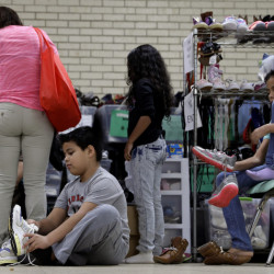 Central American migrants are fitted for shoes in the Rio Grande Valley border city of McAllen, Texas, Sunday. President-elect Donald Trump's plan to deport immigrants with criminal records sounds a lot like what the government has been doing since President Obama took office.