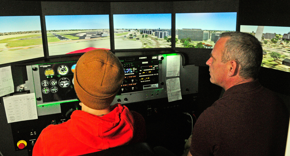 Maranacook Community High School student Tanner Evans, left, tries out the flight simulator with instructor David Russo on Friday at the University of Maine at Augusta.