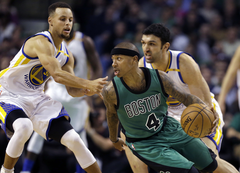 Celtics guard Isaiah Thomas looks for room to drive against Warriors guard Stephen Curry, left, and center Zaza Pachulia in the third quarter.