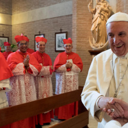 Pope Francis, second from right, talks with Pope Emeritus Benedict XVI on Saturday during a Vatican ceremony to induct new cardinals.