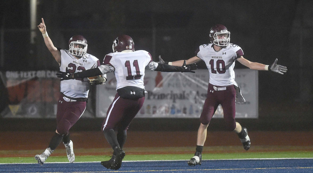 Eli Bussell, left, of Maine Central Institute celebrates after he scored a last-second touchdown to beat Lisbon 20-14 in the Class D state championship game Saturday night at Fitzpatrick Stadium in Portland.