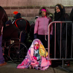 Maryam Alhamdany, 11, of Portland, sits on the ground swathed in blankets as she waits to get into Best Buy for Black Friday at the Maine Mall.