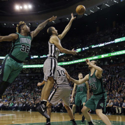 Spurs guard Manu Ginobili gets a shot off between Celtics guard Marcus Smart, left, and center Kelly Olynyk in the first half of the Spurs' 109-103 win Friday in Boston.