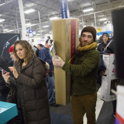 Andrew Moser of Portland carries a TV to the check-out line at Best Buy just after midnight Friday at the Maine Mall. Stores were awash in Black Friday shoppers, as retailers throughout Maine opened at midnight to lure customers with door-busting deals. The annual shopping extravaganza that extends into the weekend is the kickoff to a national holiday shopping season that analysts believe will top $1 trillion. (Brianna Soukup/Staff Photographer)