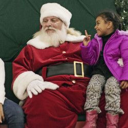 Santa Claus chats with sisters Ameena, left, Fatima and Noralhuda Almohammed at The Maine Mall in South Portland. The sisters, who are Muslim, do not celebrate Christmas, but said they wish Santa Claus would give them presents.