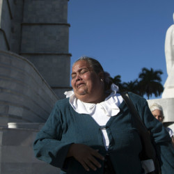 A woman weeps as she walks past the monument to independence hero Jose Marti, while paying her respects to the late Fidel Castro at Revolution Plaza in Havana, Cuba, Monday.