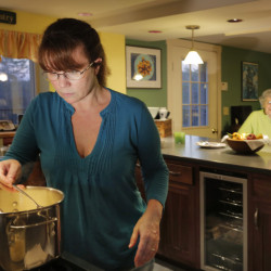 Mollie Martin spoons out cheese sauce for her grandmother, Phyllis Sanders, to taste-test. The recipe came from Sanders' husband's family.