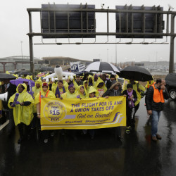 Service workers asking for $15 minimum-wage pay march on a road between terminals at Newark Liberty International Airport on Tuesday in Newark, N.J.